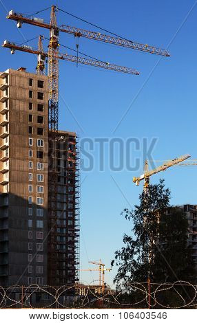 Construction cranes and built houses on blue sky background