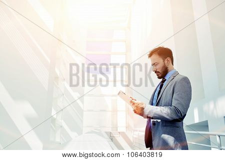 Young intelligent male using digital tablet for work