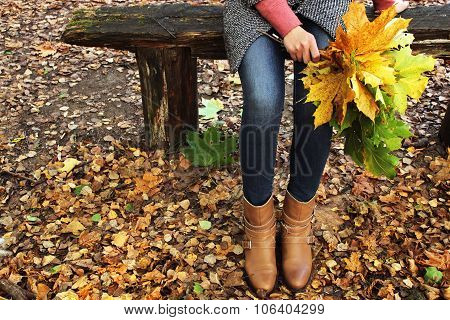 Young beautiful girl sits on a bench in a park and holding a bouquet of fallen maple leaves