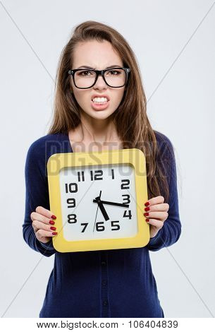 Portrait of angry woman holding wall clock isolated on a white background