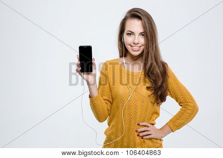 Portrait of a smiling cute woman showing blank smartphone screen isolated on a white background