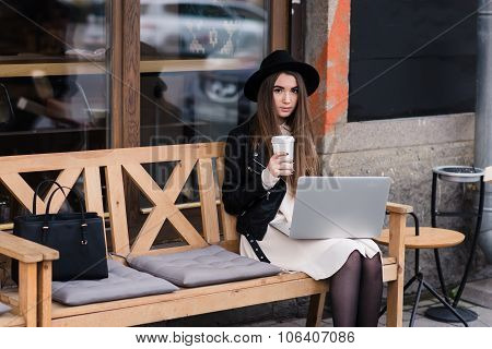 Young beautiful female enjoying coffee during work on portable laptop computer