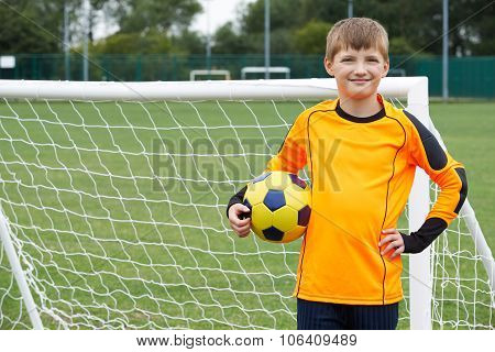 Portrait Of Goal Keeper Holding Ball On School Soccer Pitch