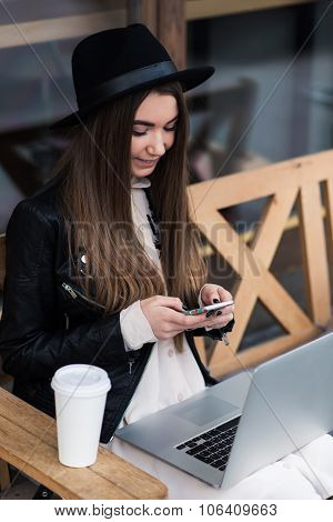 Cheerful hipster girl writing text on cell telephone during work on her net-book