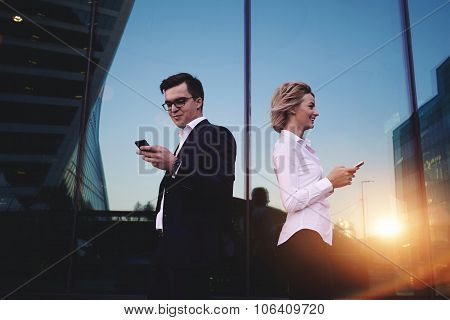 Couple of young businesspeople using cellphones standing against office building