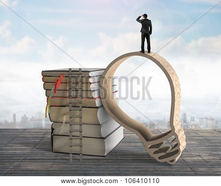 Businessman Standing On Lightbulb Shape Wooden Frame With Books