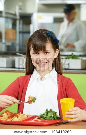Female Pupil Sitting At Table In School Cafeteria Eating Healthy Lunch