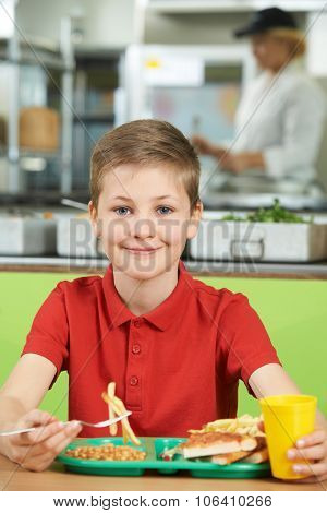 Male Pupil Sitting At Table In School Cafeteria Eating Unhealthy Lunch