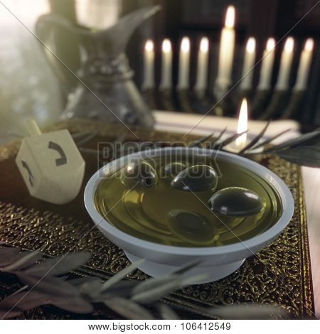hanukkah close up with candles, old books, spinning top and olives
