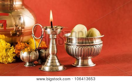 hindu puja elements, kalash diya, haldi kumkum and indian sweet pedha in silver bowl top view, isola