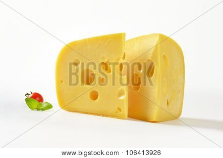 two wedges of fresh cheese on white background