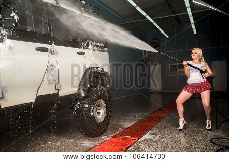Young funny woman washing offroad car