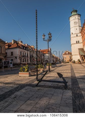 Anchor And Chain Disappearing Into The Sky. Central Square. Sandomierz