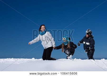 Winter fun in the deep snow - family enjoying the walk on a sunny winter day, with copy space