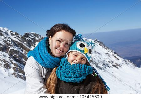 Woman and little girl portrait on a mountain top - enjoying the first snowy days high above
