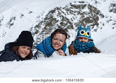 Happy family portrait in the snowy mountains on a bright sunny day