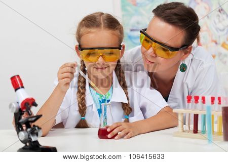 Teacher overseeing chemical experiment in elementary school science class