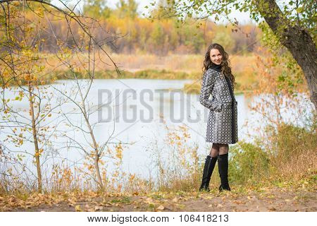 A Young Girl Walks By The River In The Autumn Forest