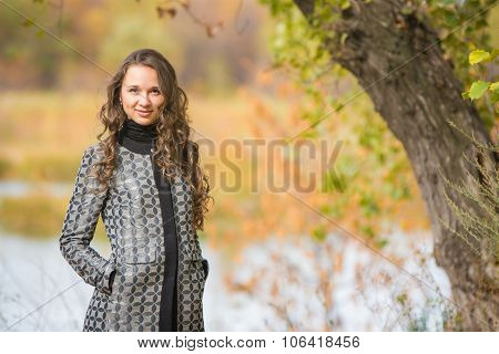 Portrait Of A Young Girl Near The Tree On A Background Of Autumn River