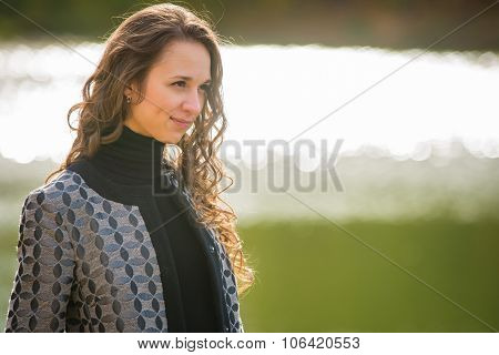 Portrait Of A Young Girl On A Background Of The River In The Cool Autumn Weather
