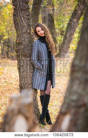 A Young Beautiful Girl Leaned Back Against The Tree In The Forest