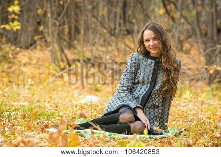 Young Beautiful Girl In A Yellow Coat Sitting On Fallen Leaves In The Forest