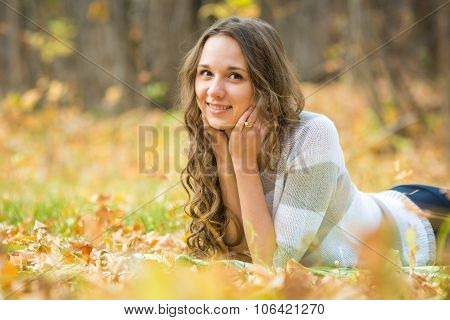 Young Beautiful Girl Lies On The Weave At A Picnic In The Autumn Forest
