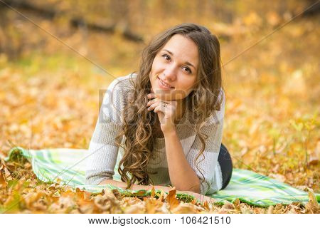 Young Beautiful Girl Lying On A Rug In The Autumn Forest