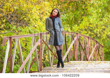 A Young Girl Stands On The Bridge Of A Warm Autumn Day