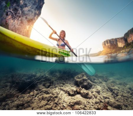 Split shot of the lady paddling the kayak in the calm tropical sea with underwater view of the bottom. Focus on the bottom only.