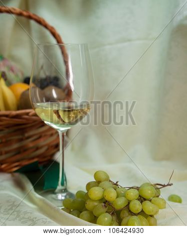 glass of white wine and fruit basket