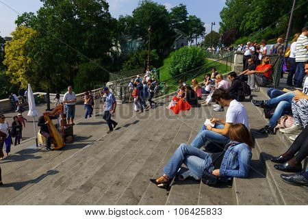 PARIS - AUGUST 10, 2015: people sit on stairs near Sacre-Cceur. The Basilica is a Roman Catholic church and minor basilica, dedicated to the Sacred Heart of Jesus, in Paris