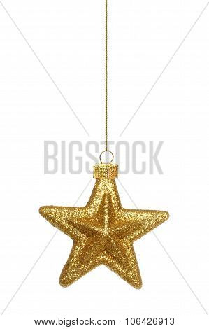 Hanging gold star Christmas ornament over white
