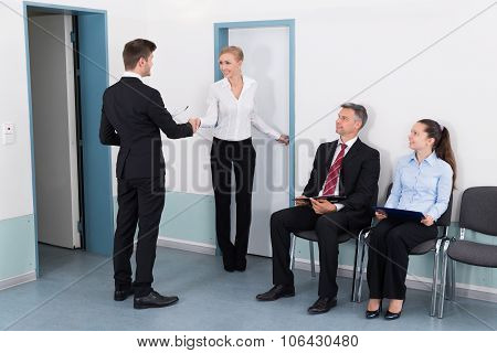 Businesswoman Shaking Hands With Man In Front Of People