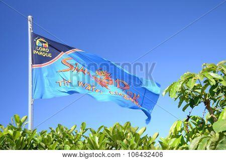 Waving flag of Siam Park against blue sky in Costa Adeje on Tenerife