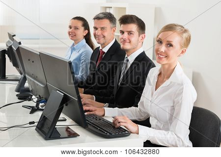 Businesspeople Typing On Desktop Computer