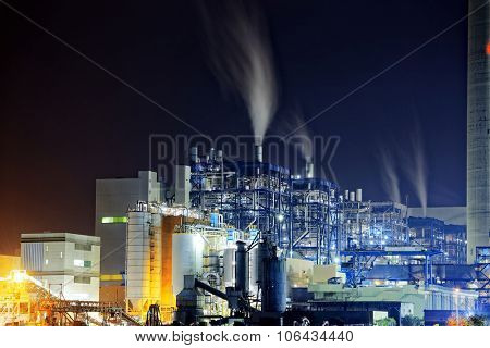 Power station with a steam cloud blown by the wind in a cold starry winter night