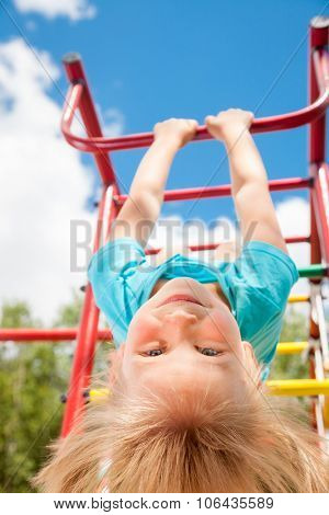 Low angle view of cute blond girl wearing blue teeshirt hanging from a monkey bars. Girl is hanging upside down looking at camera smiling. The climbing frame is located in the courtyard of a house