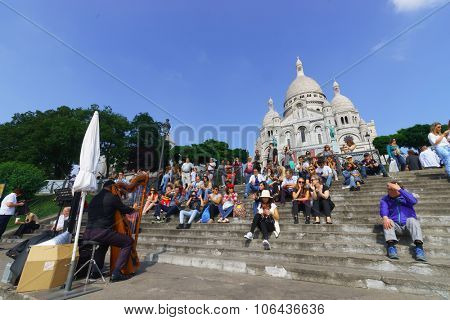 PARIS, FRANCE - AUGUST 10, 2015: people sit on stairs near Sacre-Cceur. The Basilica of the Sacred Heart of Paris, is a Roman Catholic church and minor basilica, dedicated to the Sacred Heart of Jesus