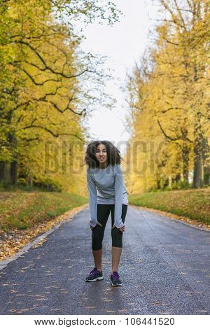 Beautiful mixed race African American girl teenager fitness running jogging in Autumn Fall trees