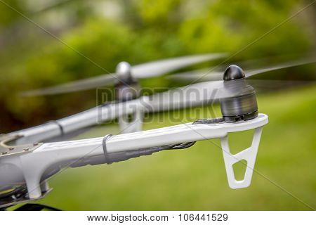 blurred spinning propellers of a hexacopter drone flying over green area