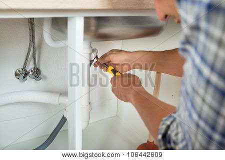 Plumber Fixing Sink Pipe With Screwdriver