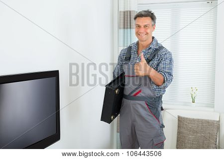 Happy Technician With Tv Set Top Box At Home