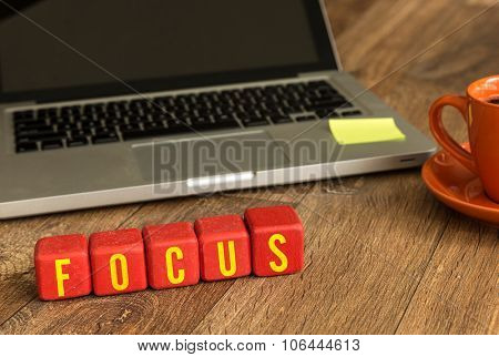 Focus written on a wooden cube in front of a laptop
