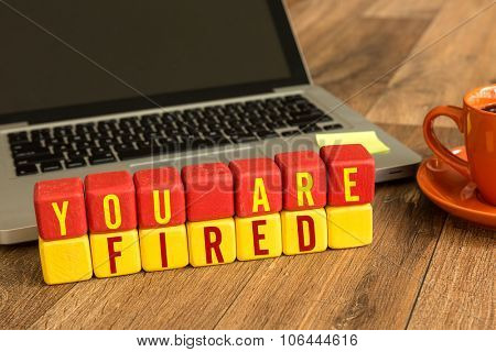 You Are Fired written on a wooden cube in front of a laptop