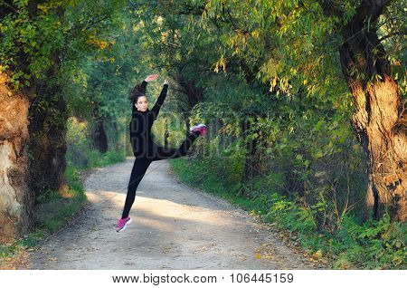 Beautiful Ballerina Girl Jumping High In The Air On Road Through Autumn Forest