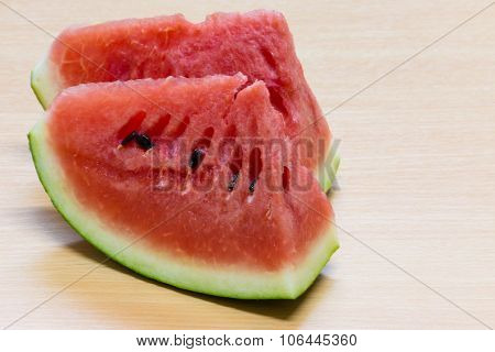 Watermelon cut to 2 pieces on the wood table, closeup the watermelon