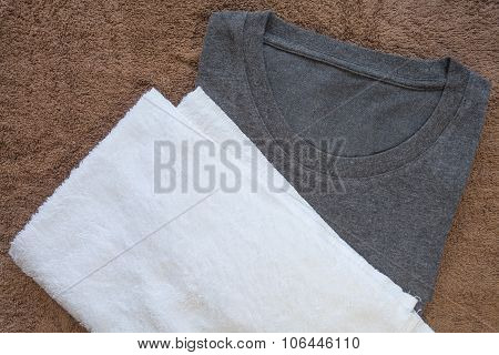 White towel and black t - shirt on brown towel background