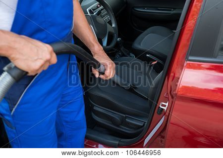 Worker Vacuuming Car With Vacuum Cleaner