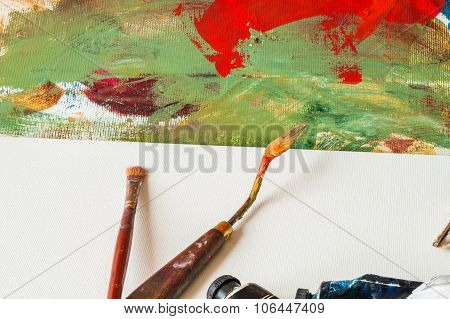 Painting Brush And A Palette Knife On Blank Canvas Desk